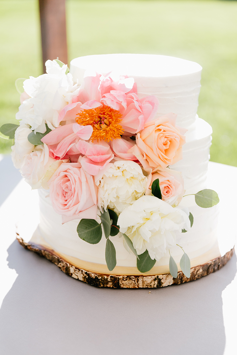 wedding cake with coral charm peonies - photo by Emily Wren Photography https://ruffledblog.com/bright-beautiful-summer-wedding-with-geometric-accents