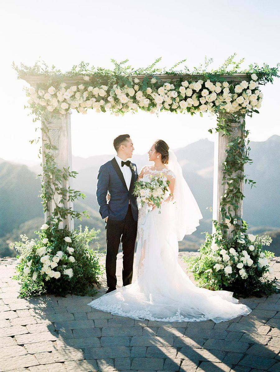 haute couture bridal gown with long sleeves and navy groom suit with elegant outdoor wedding arch backdrop