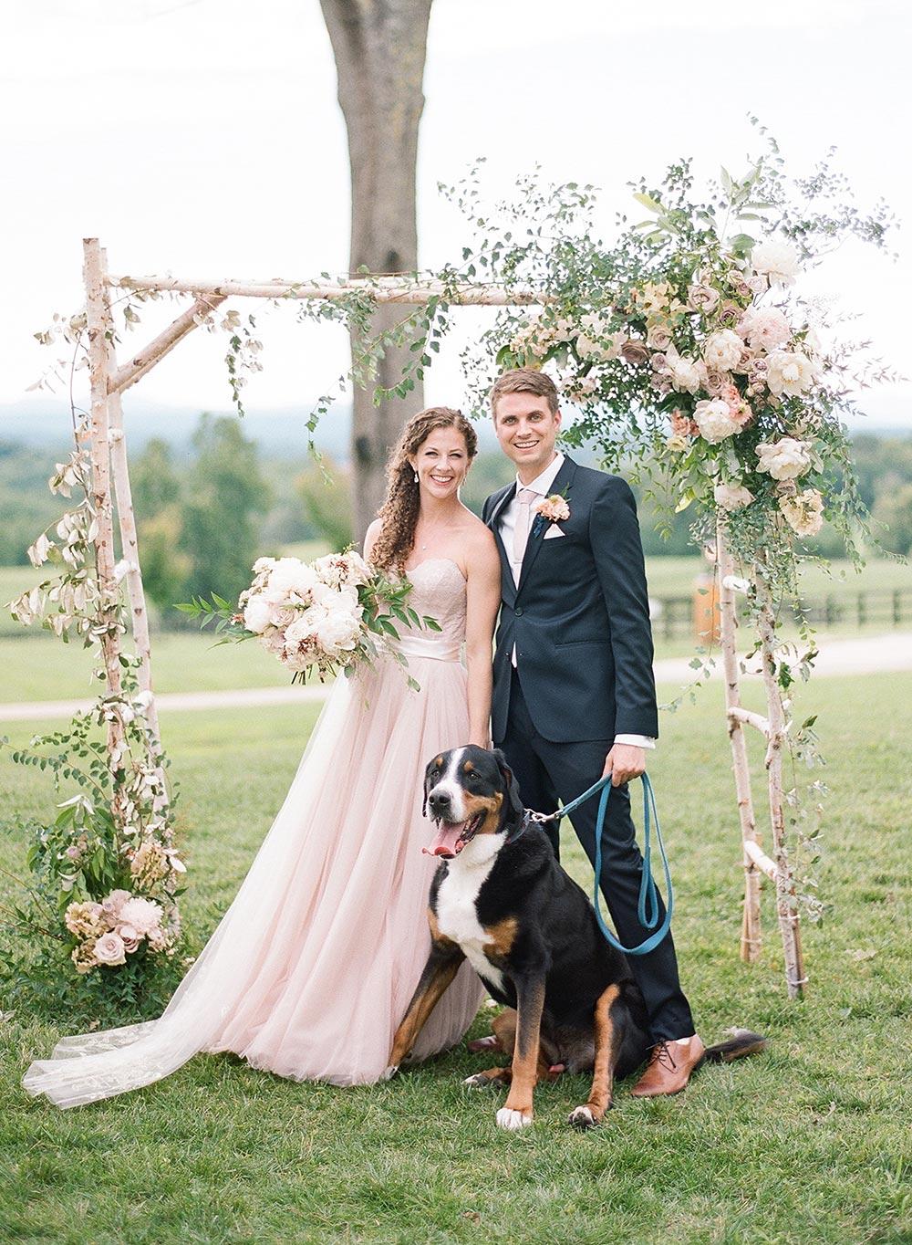 blush wedding dress and navy groom suit with birch wedding ceremony arbor