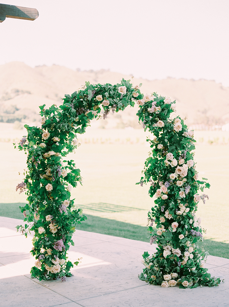 lush floral ceremony arches - photo by This Love of Yours Photography https://ruffledblog.com/charming-wedding-inspiration-with-a-lush-floral-arch
