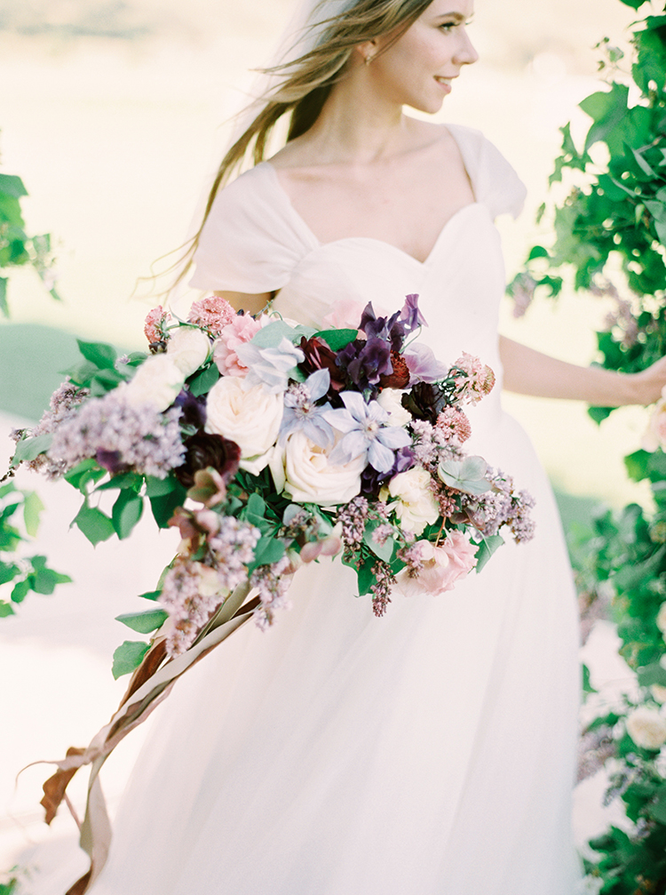 purple and ivory bouquets - photo by This Love of Yours Photography http://ruffledblog.com/charming-wedding-inspiration-with-a-lush-floral-arch