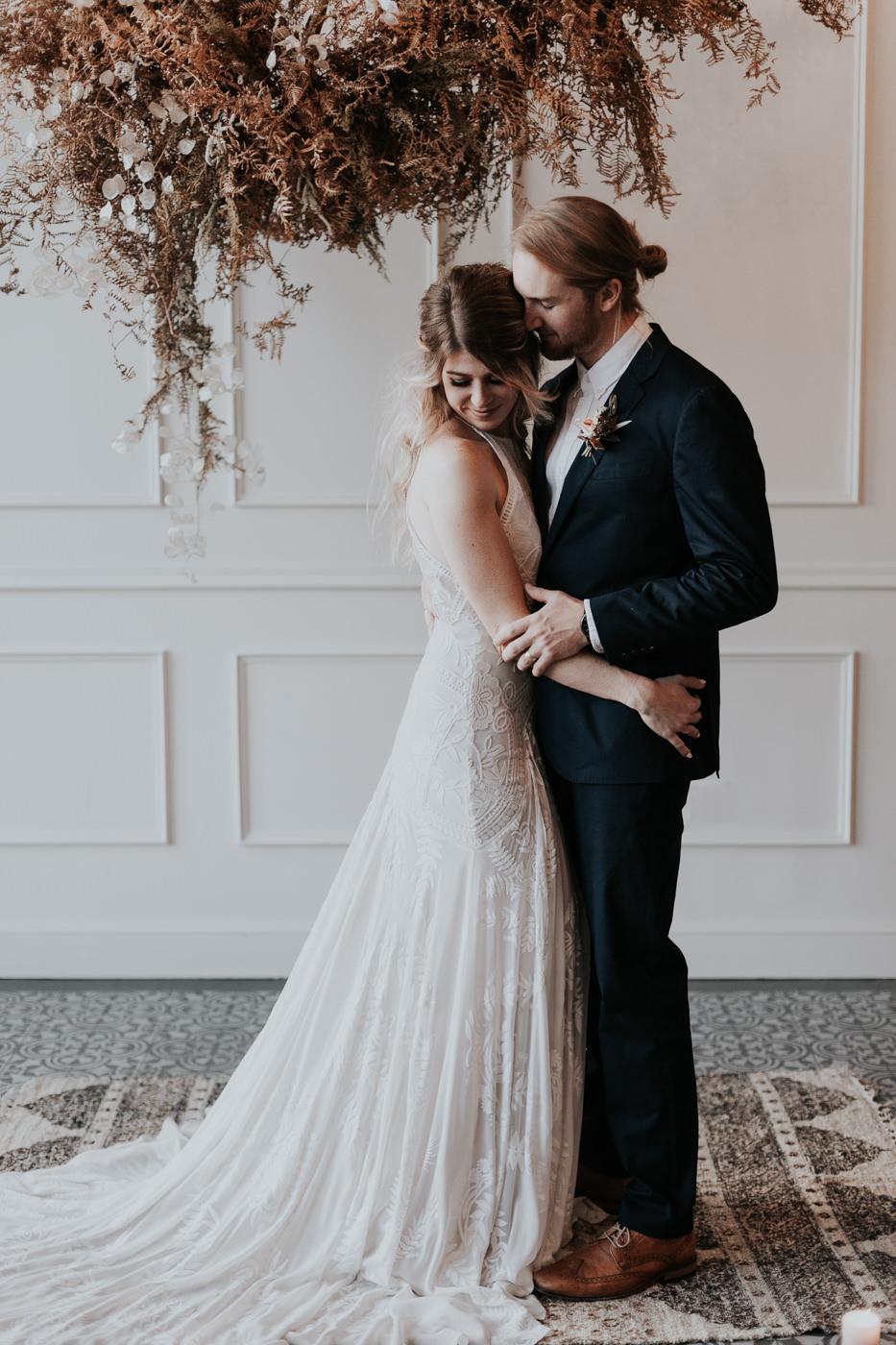 boho wedding dress and navy groom suit with dried foliage wedding ceremony backdrop