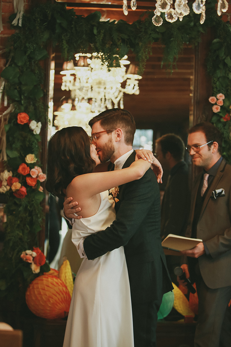 ceremony kiss - photo by Kassia Phoy https://ruffledblog.com/citrus-hued-whimsical-wedding-with-paper-details