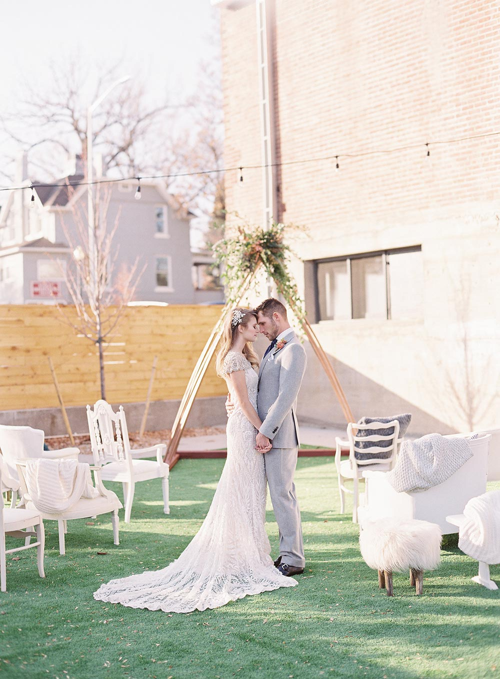 mismatched white ceremony chairs and geometric backdrop