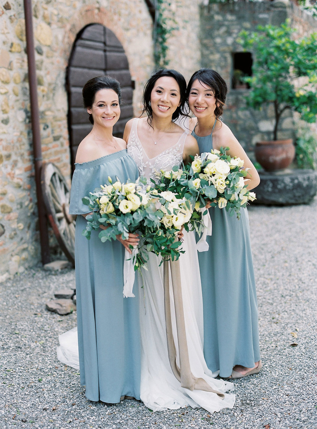 bridesmaids in dusty blue gowns - photo by Katie Grant Photography https://ruffledblog.com/classically-beautiful-intimate-wedding-in-tuscany