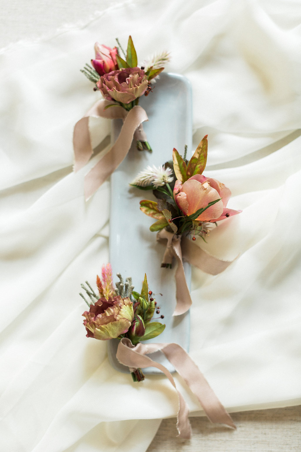 soft pink wedding boutonnieres - https://ruffledblog.com/cloudy-day-wedding-inspiration-with-a-hand-painted-bridal-gown