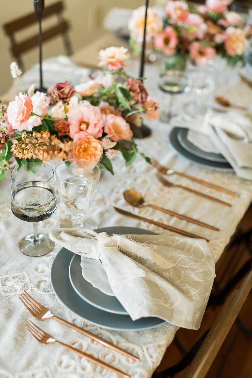 romantic wedding tablescapes with dusty blue and peachy pink - https://ruffledblog.com/cloudy-day-wedding-inspiration-with-a-hand-painted-bridal-gown