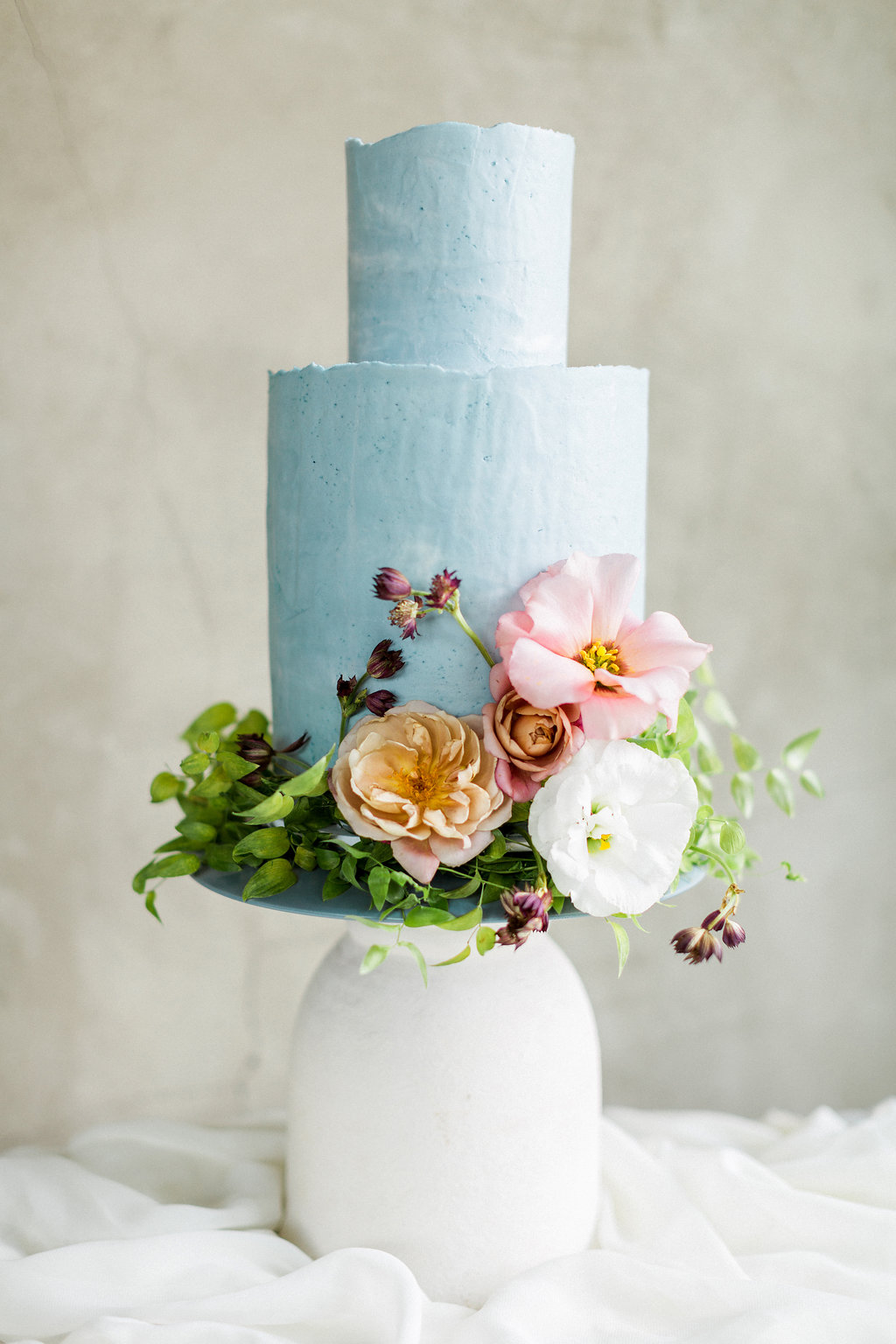 soft blue wedding cakes with flowers - https://ruffledblog.com/cloudy-day-wedding-inspiration-with-a-hand-painted-bridal-gown