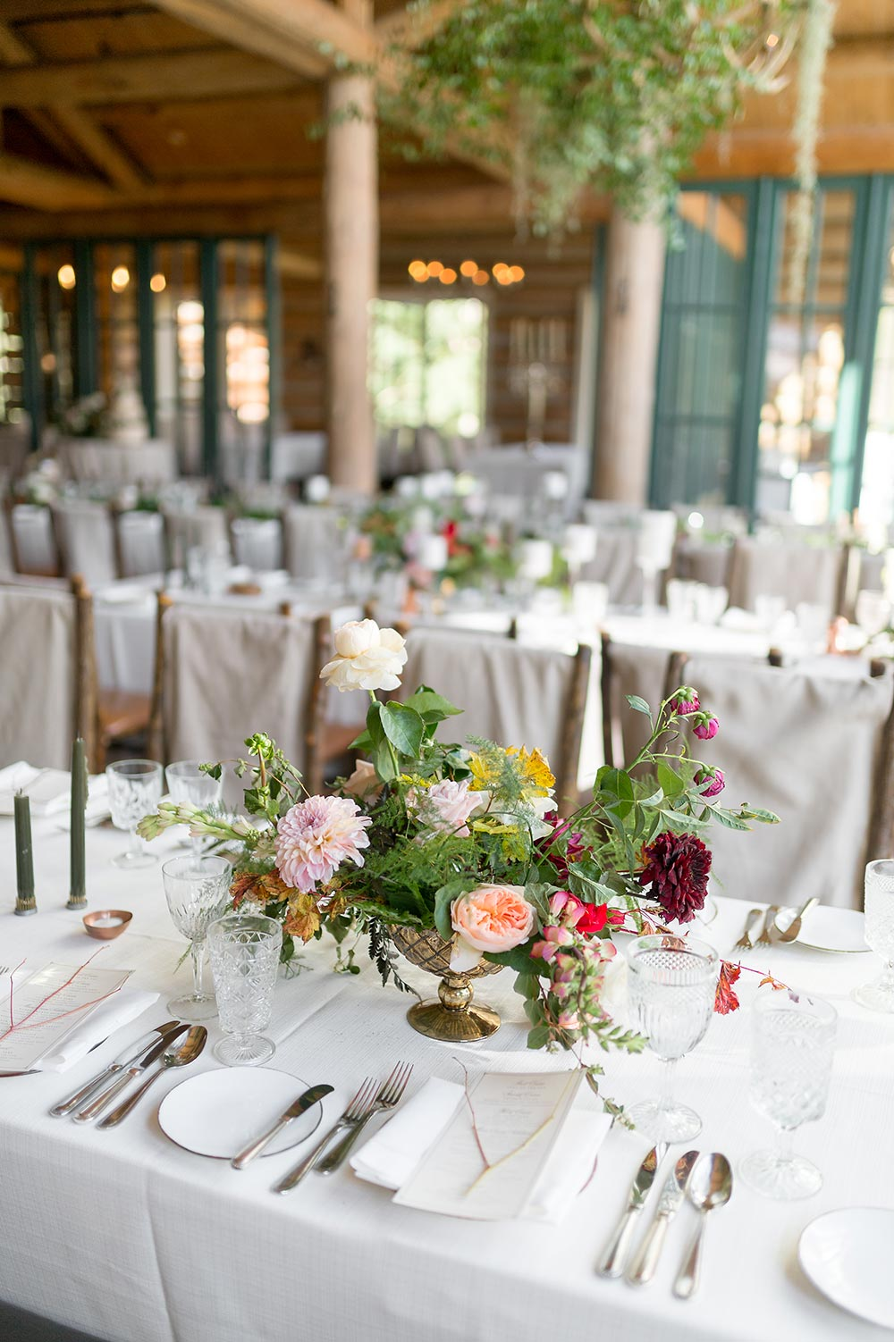 romantic cabin wedding reception decor with candles and canvas covered chairs