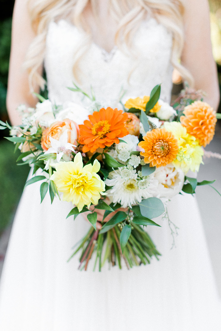 orange and yellow bouquets - photo by Erin Milnik https://ruffledblog.com/colorful-monday-afternoon-garden-elopement