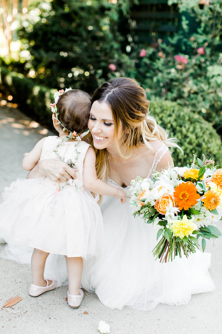 flower girl hugs at weddings - photo by Erin Milnik https://ruffledblog.com/colorful-monday-afternoon-garden-elopement