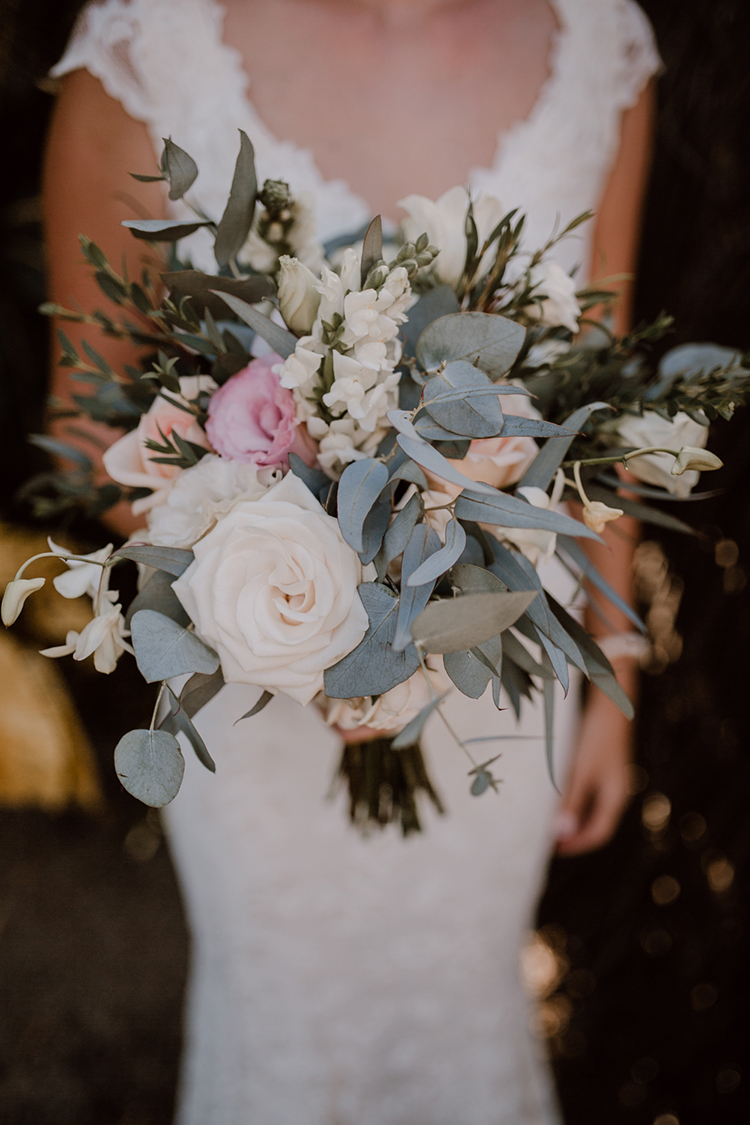 white rose and eucalyptus bouquet - https://ruffledblog.com/costa-rica-beach-wedding-with-a-cute-bridesmaid-first-look