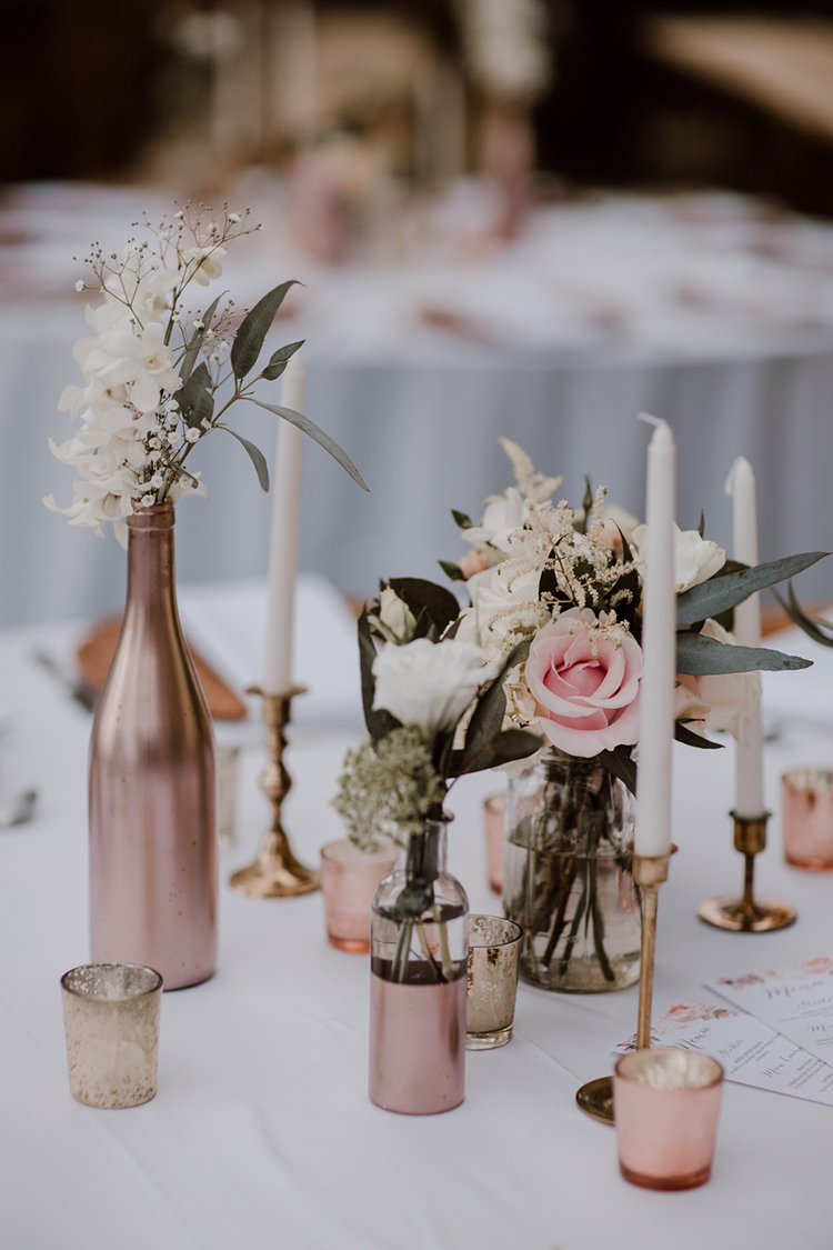 spray painted bottle centerpieces - https://ruffledblog.com/costa-rica-beach-wedding-with-a-cute-bridesmaid-first-look