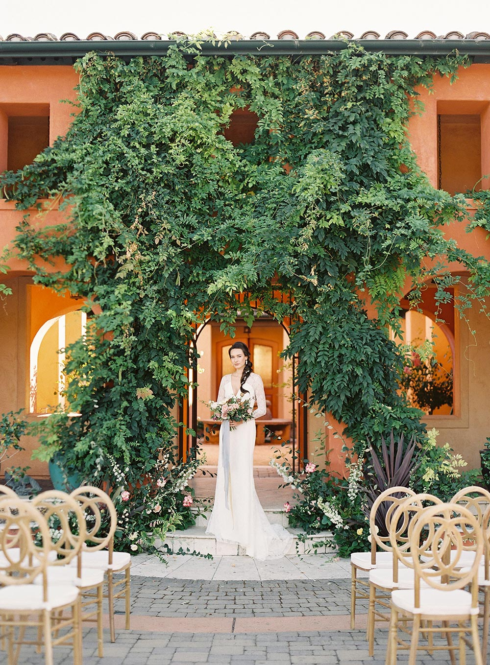 Tuscan villa wedding ceremony with natural wood chairs and long sleeve wedding dress