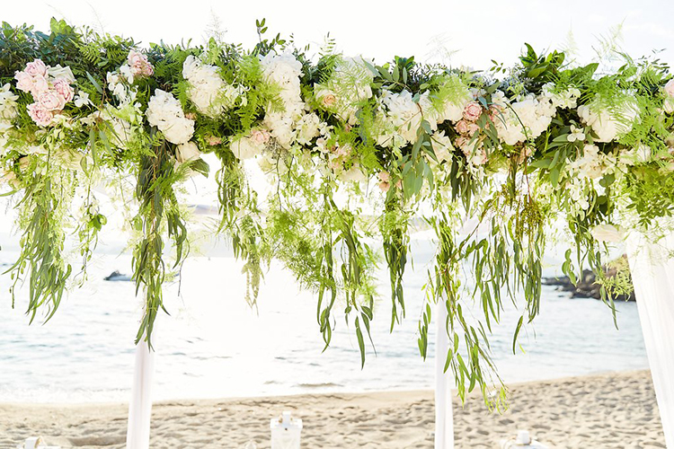 ivory ceremony arches with greneery - photo by Sotiris Tsakanikas https://ruffledblog.com/destination-wedding-in-mykonos-with-endless-hanging-lanterns