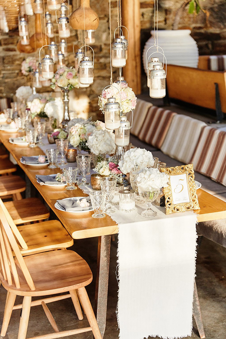 wedding reception tables - photo by Sotiris Tsakanikas https://ruffledblog.com/destination-wedding-in-mykonos-with-endless-hanging-lanterns