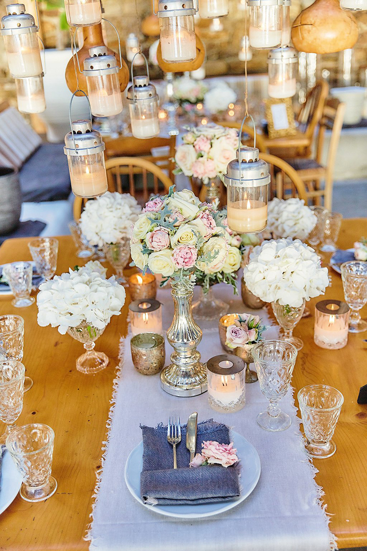 wedding reception tables with blue runners - photo by Sotiris Tsakanikas https://ruffledblog.com/destination-wedding-in-mykonos-with-endless-hanging-lanterns