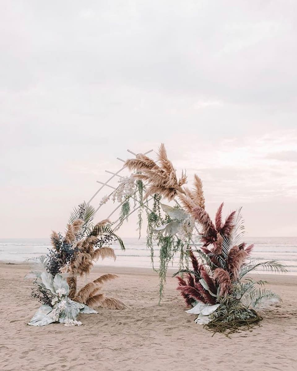 dyed flower wedding backdrop with pampas grass for a beach wedding