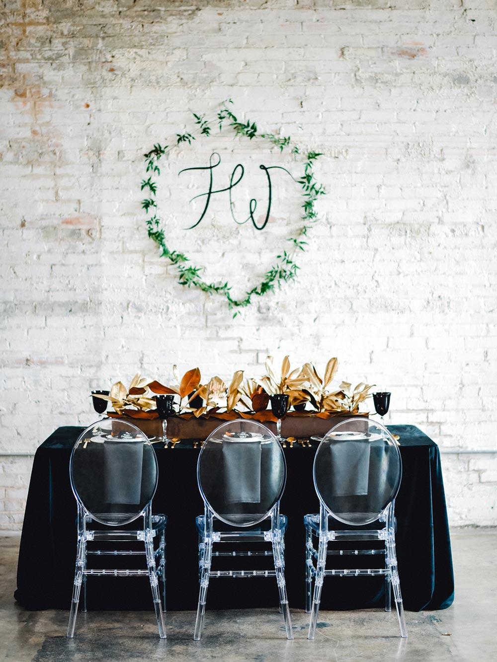 modern black wedding tablescape with greenery monogrammed wedding crest