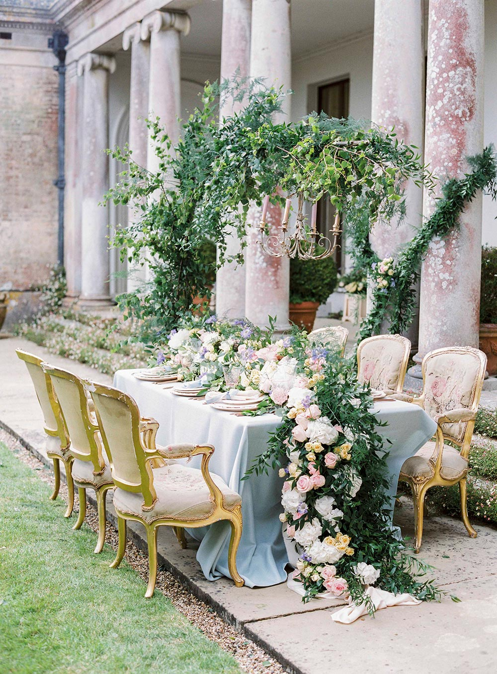 lush wedding tablescape with spring flowers and blue linens