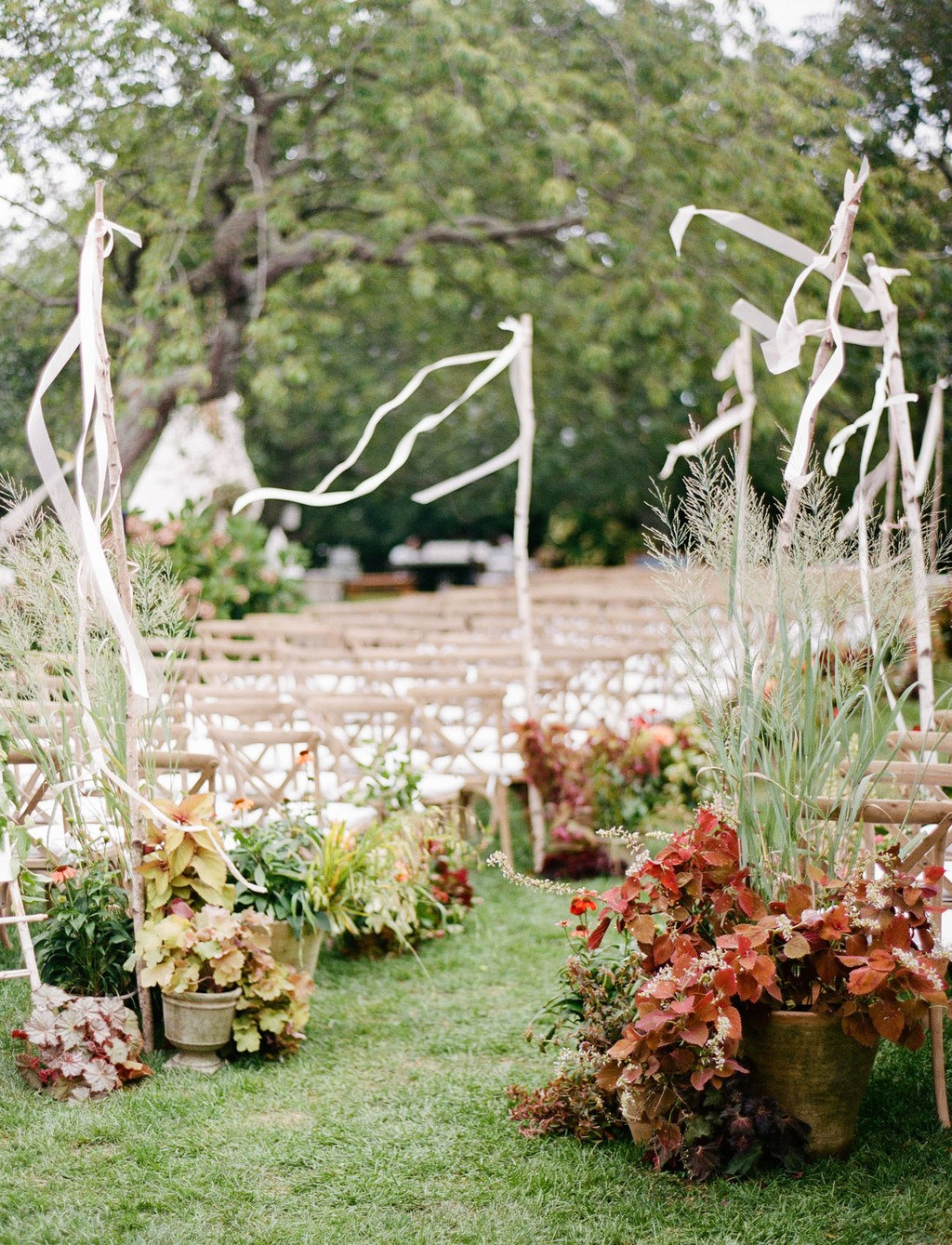 fall wedding aisle with planted arrangements and ribbon stakes
