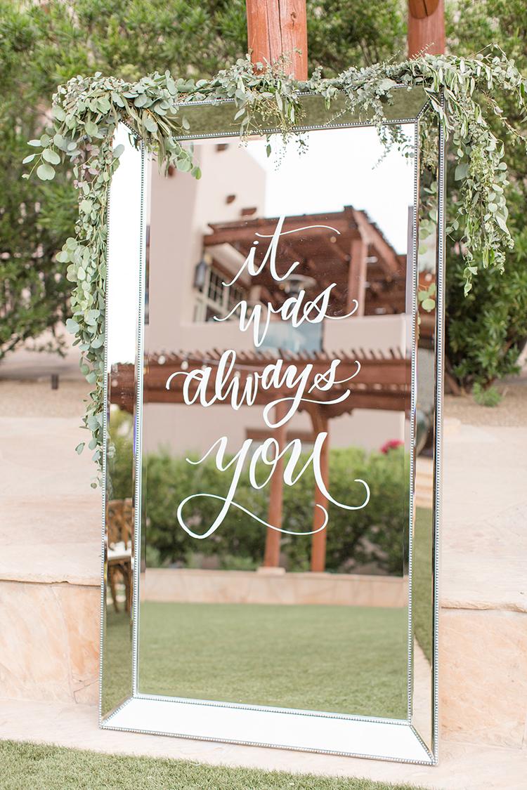 mirrored wedding signs - photo by Amy and Jordan Photography http://ruffledblog.com/feminine-floral-wedding-in-the-arizona-desert