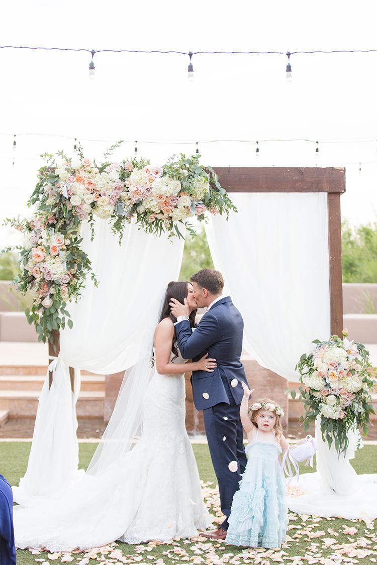 ceremony kiss - photo by Amy and Jordan Photography http://ruffledblog.com/feminine-floral-wedding-in-the-arizona-desert