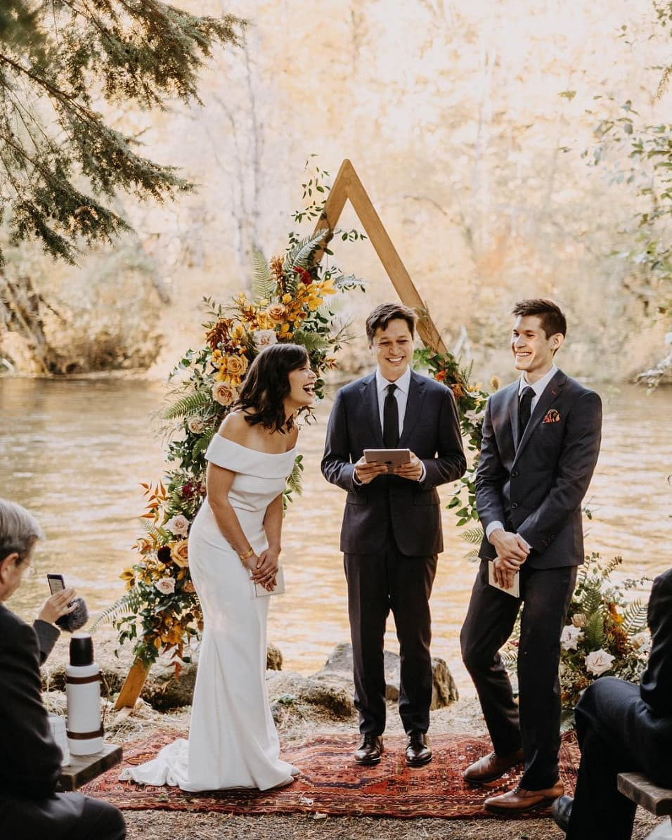 boho wedding ceremony on a creek with an off-the-shoulder wedding dress