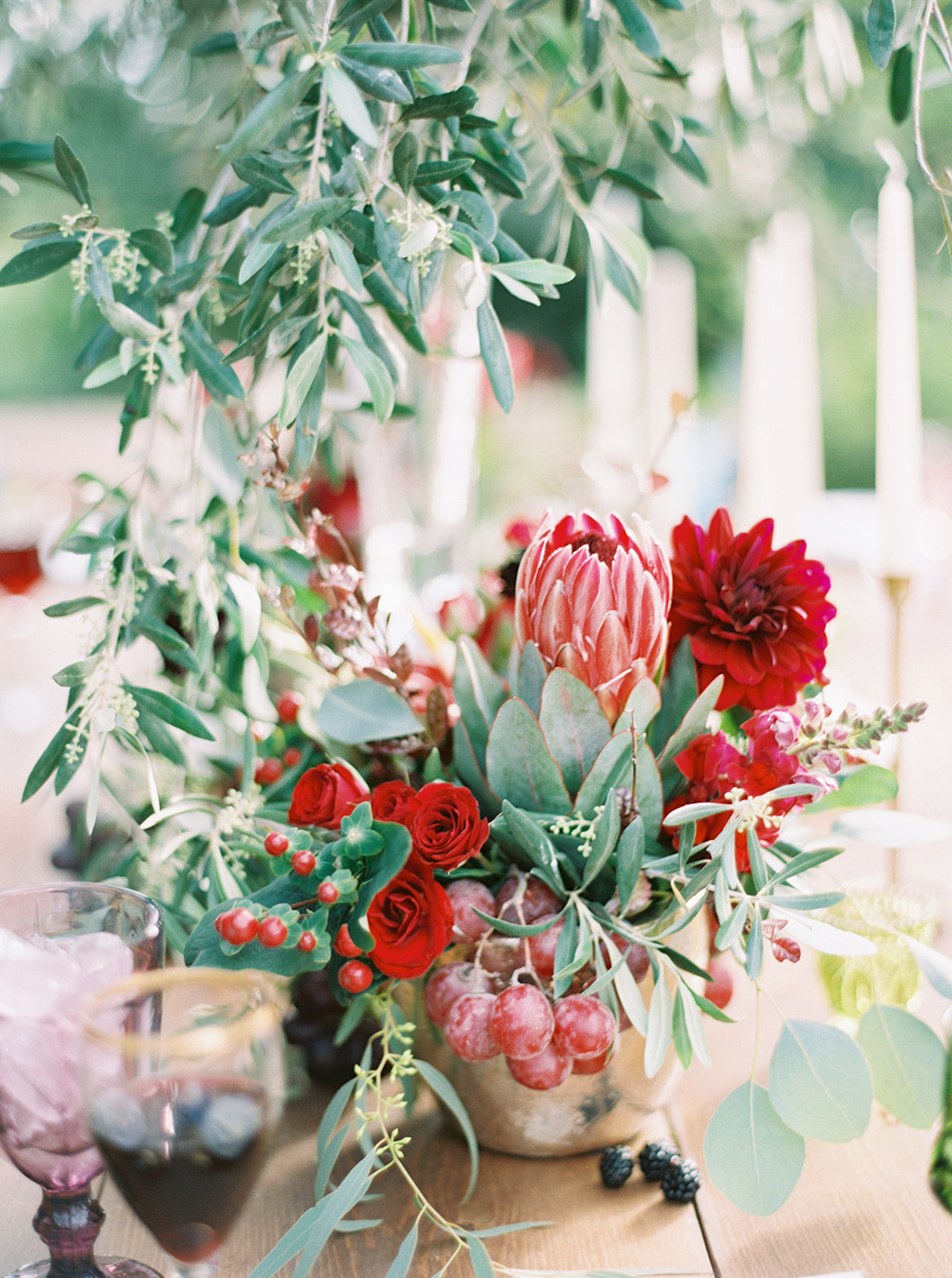 red centerpieces - photo by Melissa Jill http://ruffledblog.com/fruit-filled-vineyard-wedding-inspiration