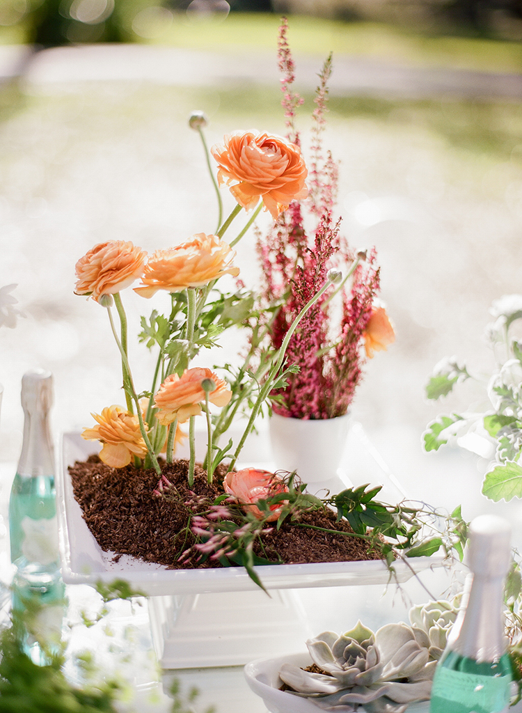 orange ranunculus centerpieces - photo by Arte de Vie http://ruffledblog.com/garden-bridal-shower-with-hanging-umbrellas