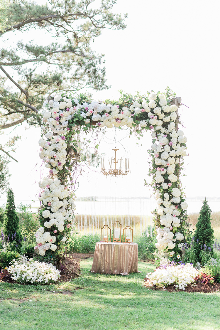 floral ceremony arches - photo by A.J. Dunlap Photography https://ruffledblog.com/glamorous-seaside-soiree-wedding-with-glam-details