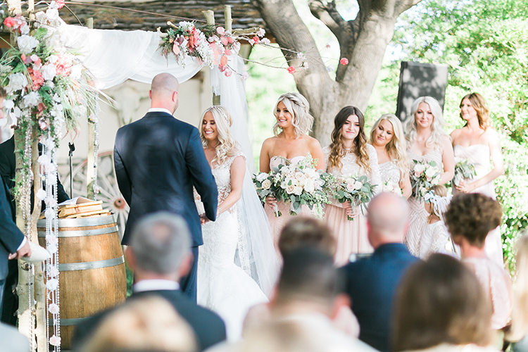 rustic wedding ceremony with floral arch - photo by J Anne Photography http://ruffledblog.com/rustic-chic-las-vegas-garden-wedding-in-pink
