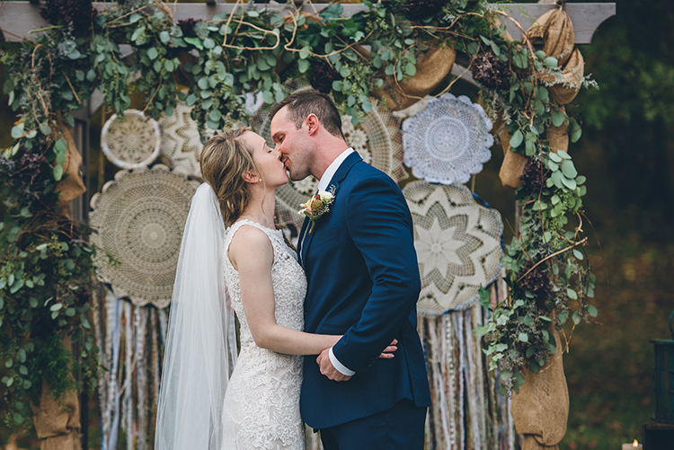 ceremony kiss - photo by Ed and Aileen Photography https://ruffledblog.com/handcrafted-wedding-with-a-doily-hoop-ceremony-backdrop