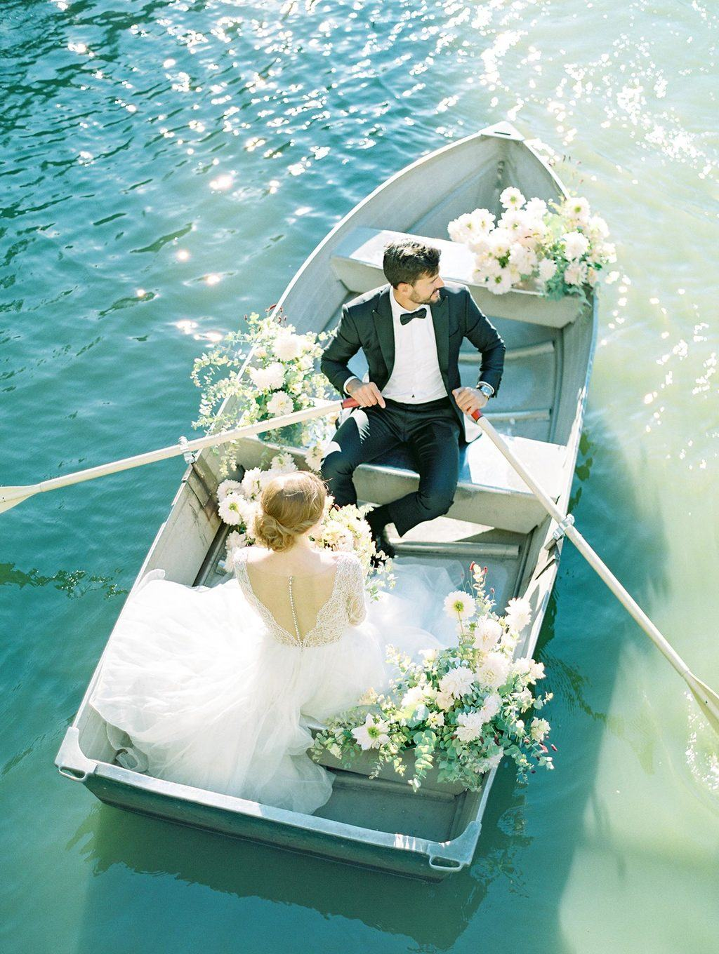 tulle and lace bridal gown with black groom tux row boat elopement