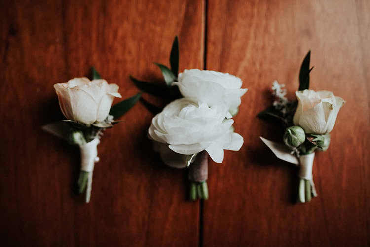 simple ranunculus boutonnieres - photo by By Amy Lynn Photography https://ruffledblog.com/industrial-loft-wedding-with-a-geometric-ceremony-backdrop