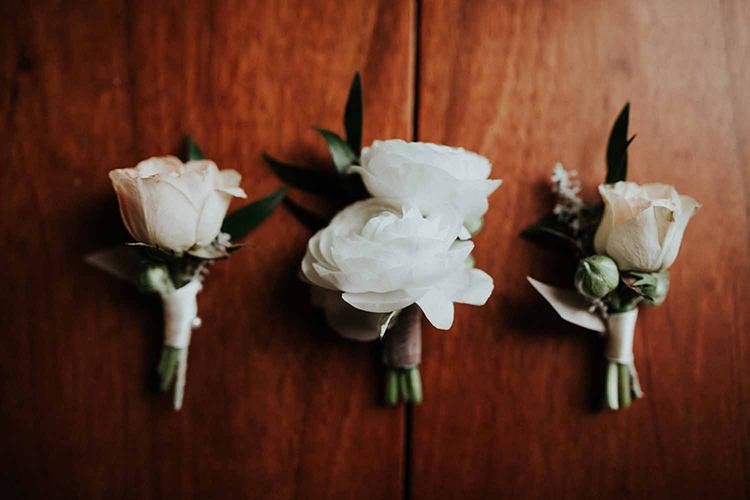 simple ranunculus boutonnieres - photo by By Amy Lynn Photography http://ruffledblog.com/industrial-loft-wedding-with-a-geometric-ceremony-backdrop
