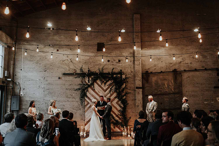 industrial wedding ceremonies at Luce Loft - photo by By Amy Lynn Photography https://ruffledblog.com/industrial-loft-wedding-with-a-geometric-ceremony-backdrop