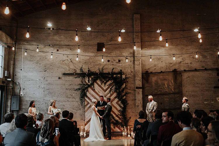industrial wedding ceremonies at Luce Loft - photo by By Amy Lynn Photography http://ruffledblog.com/industrial-loft-wedding-with-a-geometric-ceremony-backdrop