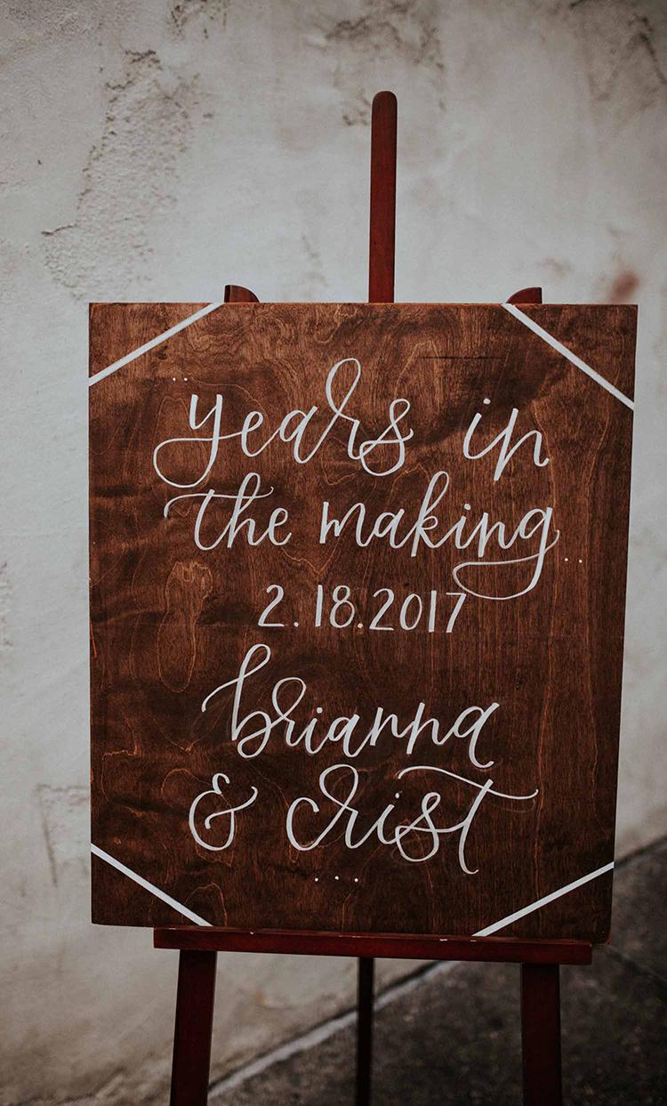 wood wedding signage - photo by By Amy Lynn Photography https://ruffledblog.com/industrial-loft-wedding-with-a-geometric-ceremony-backdrop