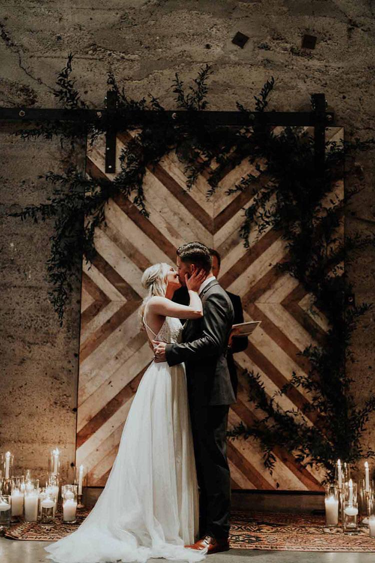ceremony kiss - photo by By Amy Lynn Photography http://ruffledblog.com/industrial-loft-wedding-with-a-geometric-ceremony-backdrop