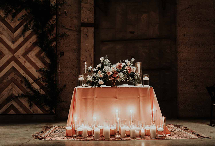 candlelit sweetheart tables - photo by By Amy Lynn Photography http://ruffledblog.com/industrial-loft-wedding-with-a-geometric-ceremony-backdrop