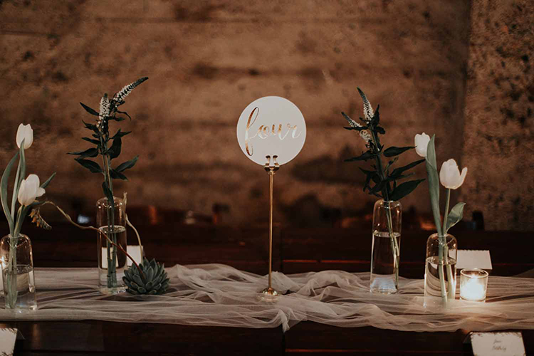 paper table numbers - photo by By Amy Lynn Photography https://ruffledblog.com/industrial-loft-wedding-with-a-geometric-ceremony-backdrop