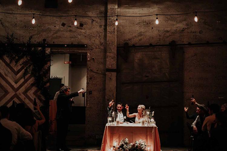 wedding toasts - photo by By Amy Lynn Photography http://ruffledblog.com/industrial-loft-wedding-with-a-geometric-ceremony-backdrop