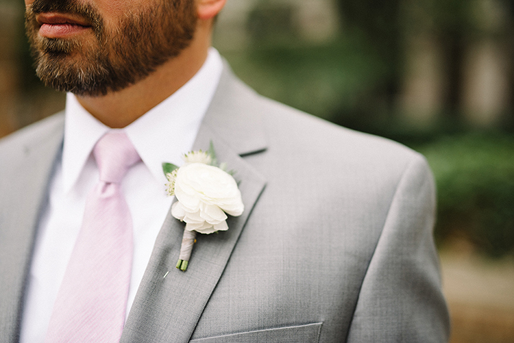 ivory boutonnieres with pink ties - photo by The Kama Photography https://ruffledblog.com/industrial-modern-wedding-with-a-greenery-wall