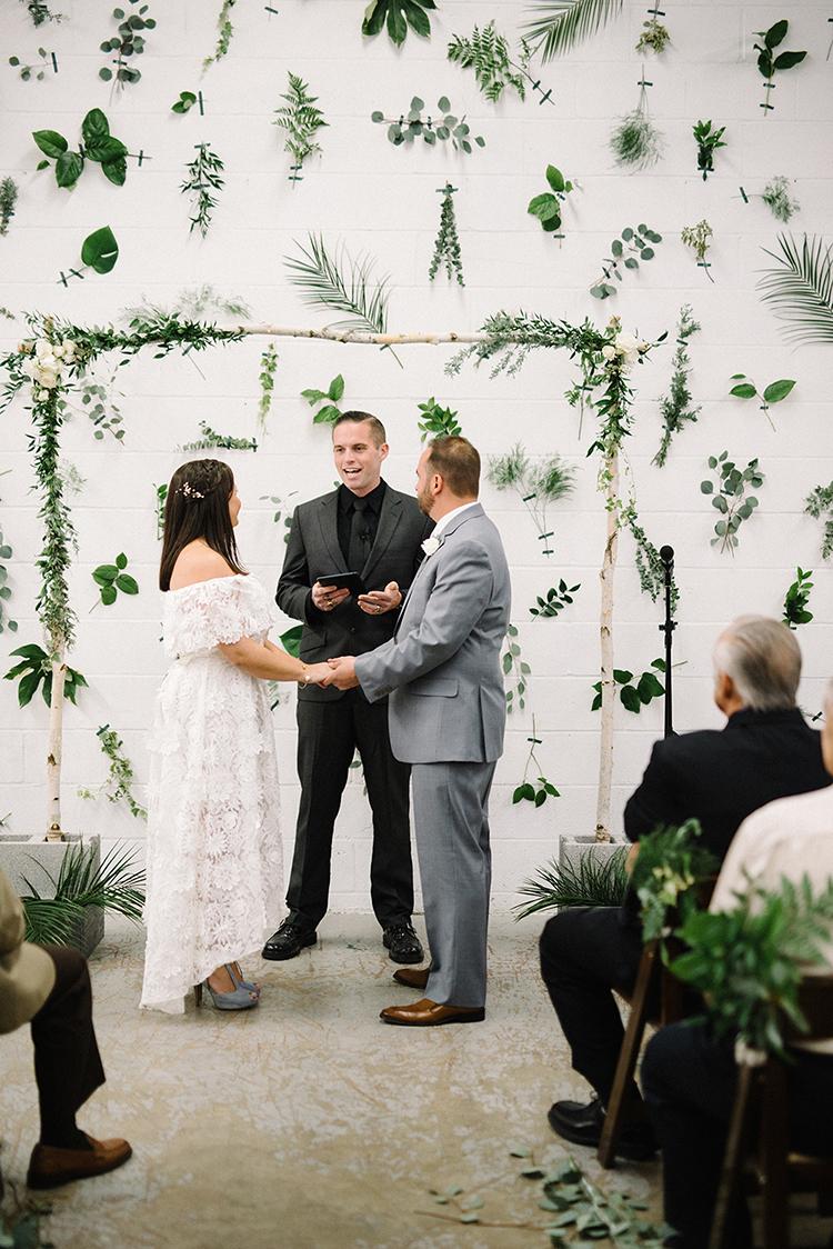 greenery backdrops for weddings - photo by The Kama Photography https://ruffledblog.com/industrial-modern-wedding-with-a-greenery-wall