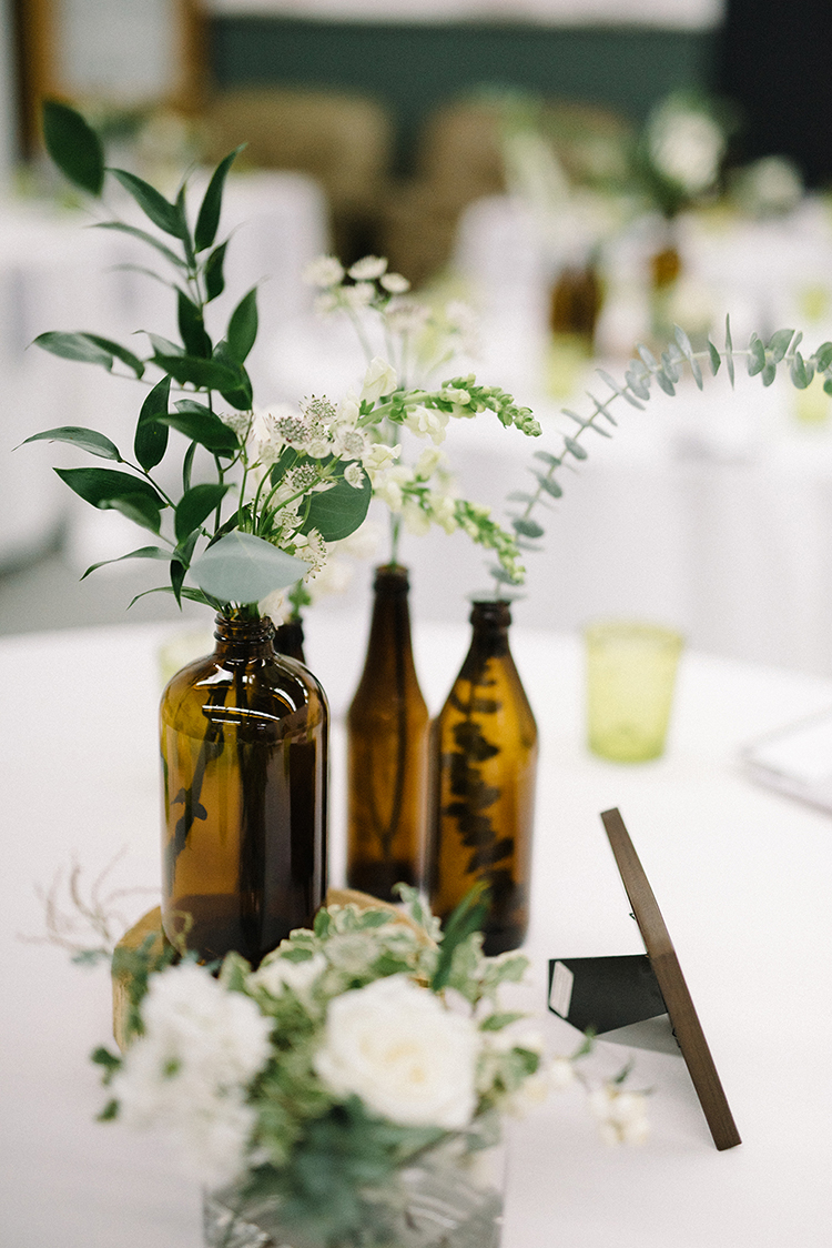 amber bottle centerpieces - photo by The Kama Photography http://ruffledblog.com/industrial-modern-wedding-with-a-greenery-wall