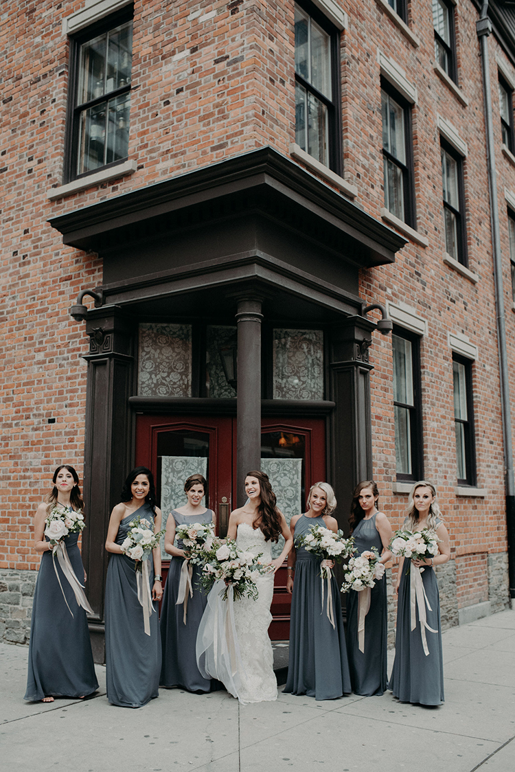 bridesmaids wearing dove grey gowns - photo by Scarlet ONeill https://ruffledblog.com/industrial-space-meets-enchanted-forest-wedding