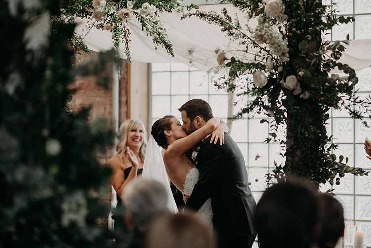 ceremony kiss - photo by Scarlet ONeill https://ruffledblog.com/industrial-space-meets-enchanted-forest-wedding