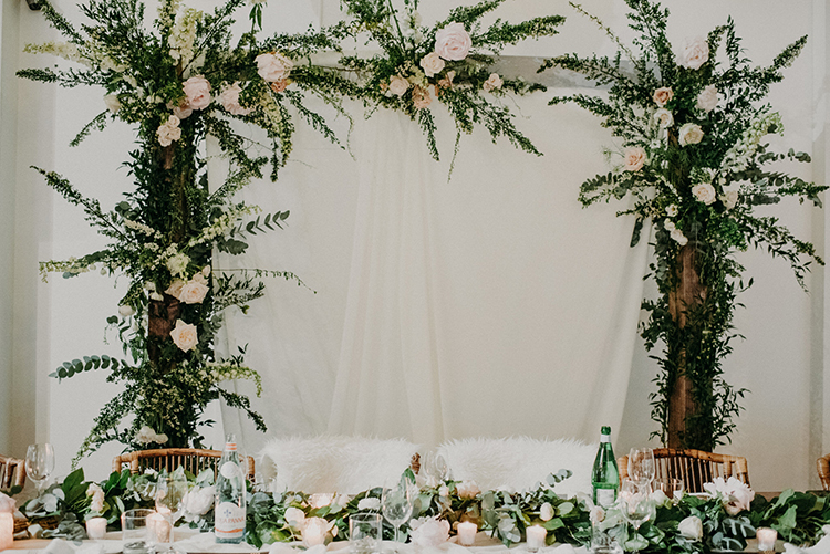 sweetheart table arches - photo by Scarlet ONeill https://ruffledblog.com/industrial-space-meets-enchanted-forest-wedding