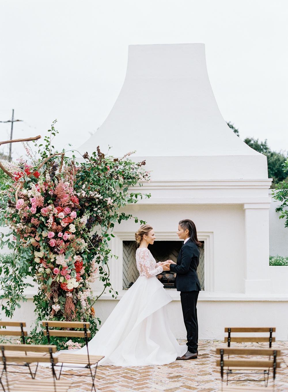 ruffled ballgown wedding dress with a black suit same sex wedding